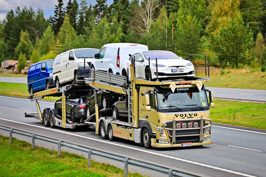 Gold Volvo FM Vehicle Carrier Hauls Cars on Motorway.