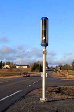 Modern roadside speed camera on a sunny day of winter  with slow traffic on road.
