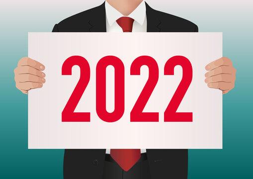 Pour présenter le bilan de son entreprise, un cadre dirigeant en costume cravate, porte une pancarte blanche sur lequel est écrit l'année 2022.