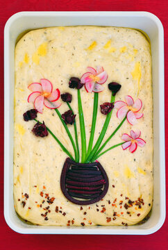 View of a focaccia bread decorated with a garden made of vegetables on top