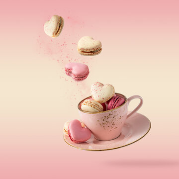 French sweet colorful cookies macarons macaroons in vintage pink cup flying isolated  on gradient yellow pink background.