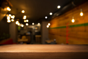 Fototapeta image of wooden table in front of abstract blurred background of restaurant lights obraz