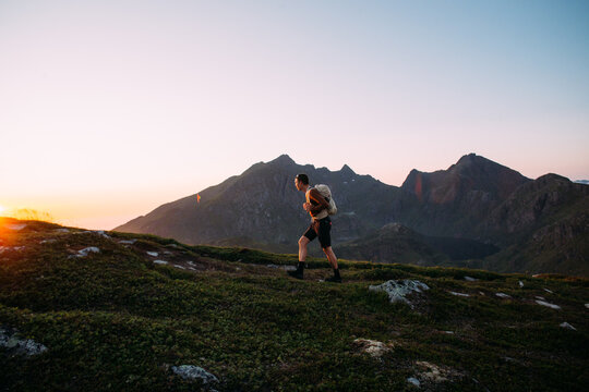 Young athletic man with backpack hike to reach summit of mountain at sunset. Cinematic beautiful adventure. Inspiring time spent outdoors. Explore norway in summer