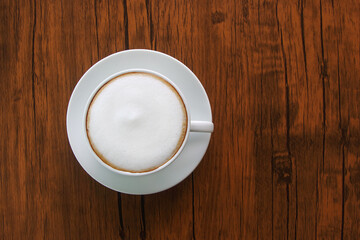cup of latte or cappuccino on brown wooden floor