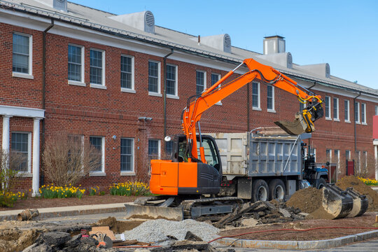 Excavator digging a trench and loading on the dump truck in Middlesex Community College in town of Bedford, Massachusetts MA, USA.