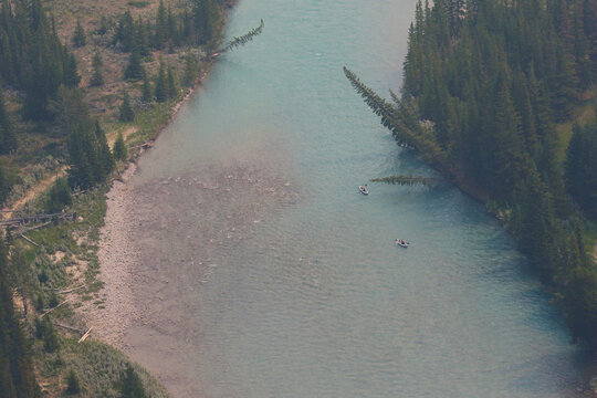 Two kayakers gliding down the Bow River just outside of Banff, Alberta.  Shot from high over head.