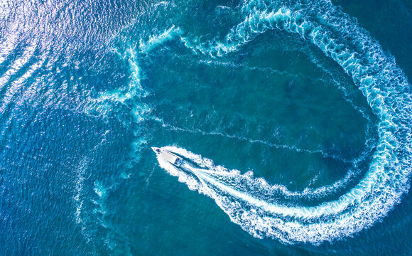 A high-speed boat or yacht maneuvers on the surface of the sea or ocean. Aerial view.