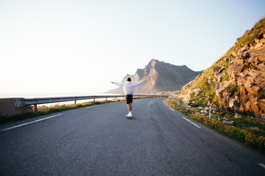Wide shot of man in oversized hoodie and shorts ride on longboard into mountain road landscape on longboard. Summer youth vibes, skateboarding into sunset. Holiday inspiration