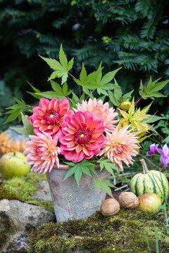 Blumenstrauß mit orange Dahlien im Terracotta-Topf im Garten
