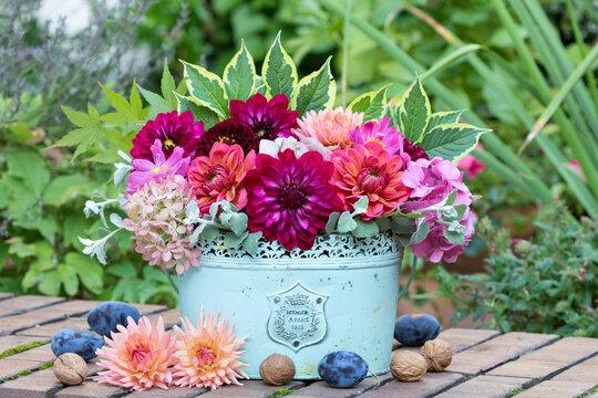 Blumenstrauß mit Dahlien und Hortensienblüten in vintage Vase als florale Dekoration