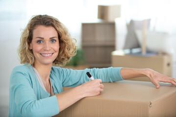 Fototapeta happy woman labeling moving box at home obraz