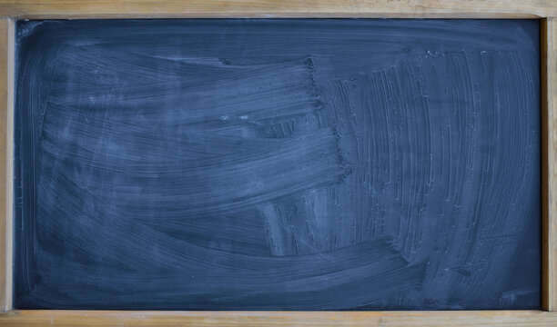 Background and texture of a black chalkboard smeared with chalk and roughly cleaned, with a wooden frame and space for a lot of text