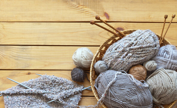 Handmade circular knitting with five needles, balls of woolen yarn and knitting needles on wooden background. Skeins of different types of beige and brown yarn in wicker basket. DIY concept