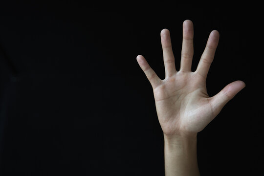Woman's palm on black background. Abused woman. Stop violence and abuse of women. International Women's Day.