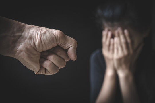 A man's hand will hurt a woman. Domestic violence and harassment of women. International Women's Day.