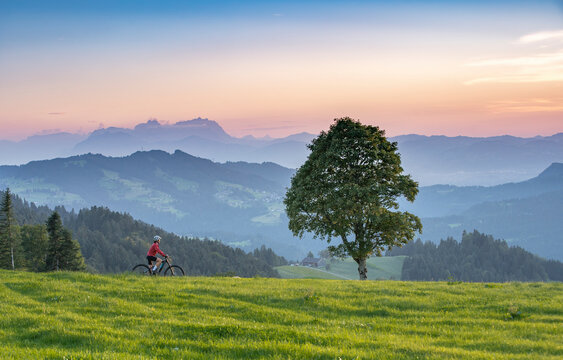 nice senior woman on electric mountain bike at sunset in the mountains of Bregenz Forest, Vorarlberg, Austria with Saentis summit in Switzerland in the background