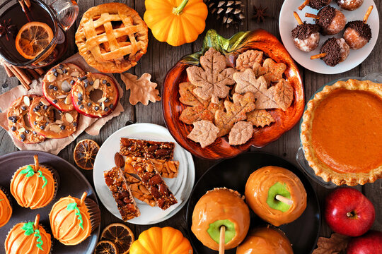 Fall desserts table scene with a mixture of sweet autumn treats. Top down view over a dark wood background.