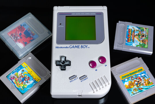 Fukuoka, Japan - september 19, 2021 : the original nintendo game boy released in Japan in 1989 with various game cartridges isolated on black background