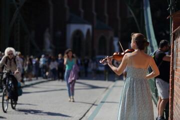 Fototapeta Piękna moda dziewczyna, skrzypaczka gra na skrzypcach na moście we Wrocławiu. obraz