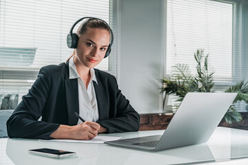 Obraz Businesswoman wearing formal suit is sitting at workplace and li - fototapety do salonu