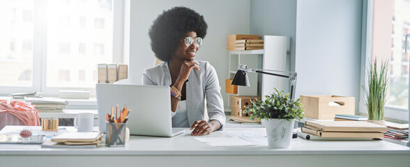 Fototapeta Attractive young African woman holding hand on chin and smiling while sitting at her working place in office obraz