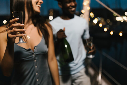 Biracial couple having party and dancing with friends while drinking champagne and celebrating new year eve - Focus on glass