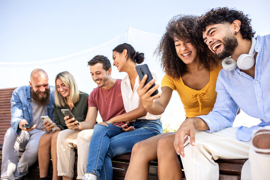Diverse group of happy college friends using mobile phone while sitting together outdoors - Happy smiling young students watching and sharing content on social media app - Youth and technology concept