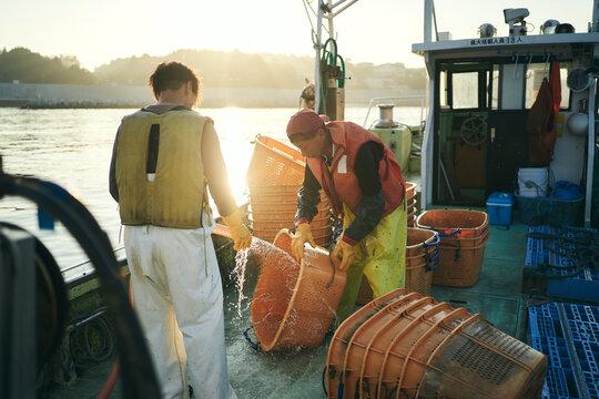 寄港する漁船で片付けをする漁師