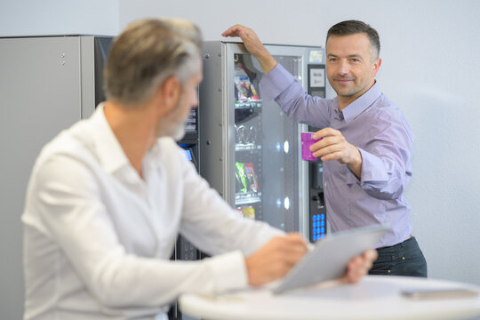 businessman offering colleague a drink from vending machine