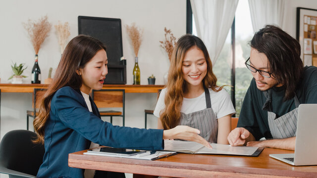 Cheerful Asian small business owners couple meeting with consultant talking about business plan and finance in cafe. Young Japanese agent consider signing contract insurance together at restaurant.