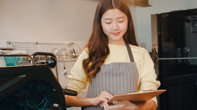 Portrait young Asian lady barista take receive order with menu feeling happy at urban cafe. Asia small business owner girl in apron relax toothy smile looking to camera stand at counter in coffee shop