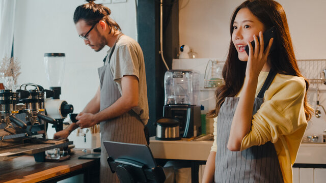 Young Asia female barista taking order by mobile phone and digital tablet standing behind bar counter while talking with customer on mobile phone at cafe restaurant. Owner small business concept.