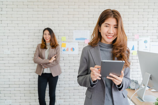 Two Asian young creative businesswomen holding a cup of coffee, working on laptop and disscuss about work while working in office. Casual business, freelance work at cafe, social meeting concept.