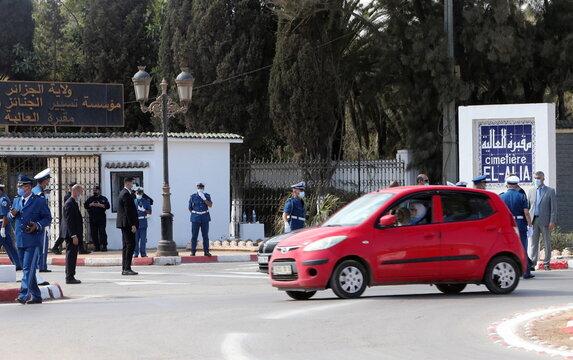 Police members stand outside El Alia cemetery in Algiers