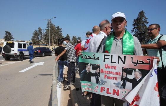 People stand near El Alia cemetery, in Algiers