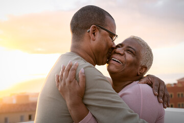 Obraz Happy Latin senior couple having romantic moment embracing on rooftop during sunset time - Elderly people love concept - fototapety do salonu