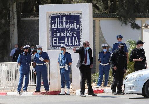Police members stand outside El Alia cemetery, in Algiers