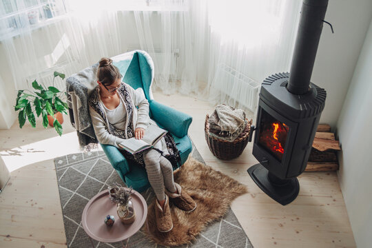 woman sitting in a cozy armchair with a warm blanket reading a b