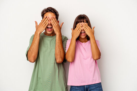 Young mixed race couple isolated on white background covers eyes with hands, smiles broadly waiting for a surprise.