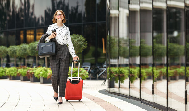Young happy stylish business woman in formal outfit with suitcase walking along city street