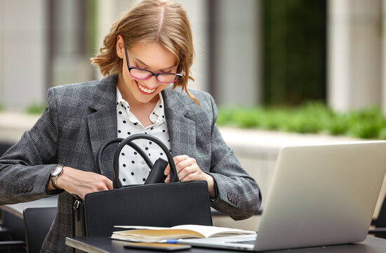 Happy businesswoman looking for something in handbag while working outside with laptop