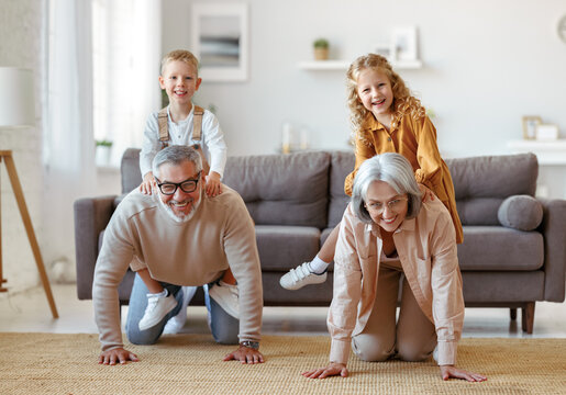 Active positive senior grandparents carrying excited little kids grandchildren on backs