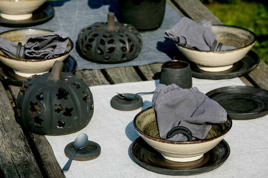 Rustic table setting outside in garden with empty craft ceramic tableware