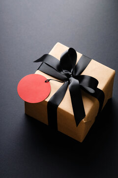 Gift box with black bow and red price tag on black background.
