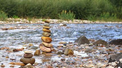 Piramida, wieża ułożona z kamyków w górskim potoku. Mountain stream