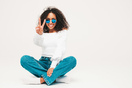 Beautiful black woman with afro curls hairstyle.Smiling model in sweater and trendy jeans clothes. Sexy carefree female sitting on white background in studio. Tanned and cheerful  in sunglasses