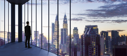 Businessperson in empty office looking out of panoramic window with bright city downtown and sky...