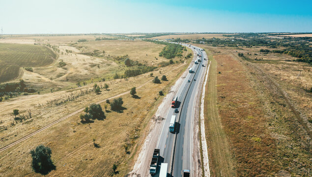 Logistics cargo transportation concept. Many freight cargo trucks drive on highway among cars, aerial view.