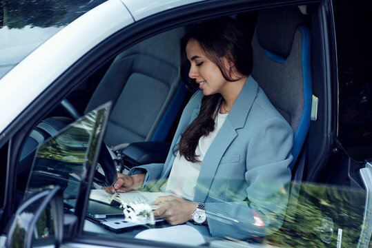 Attractive young woman taking a coffee break. Successful businesswoman with laptop, notebook and smartphone sitting in the car.