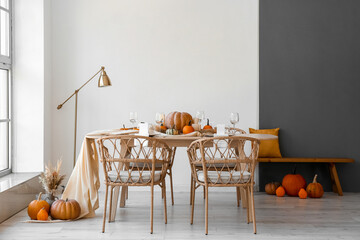 Dining table with pumpkins in interior of room
